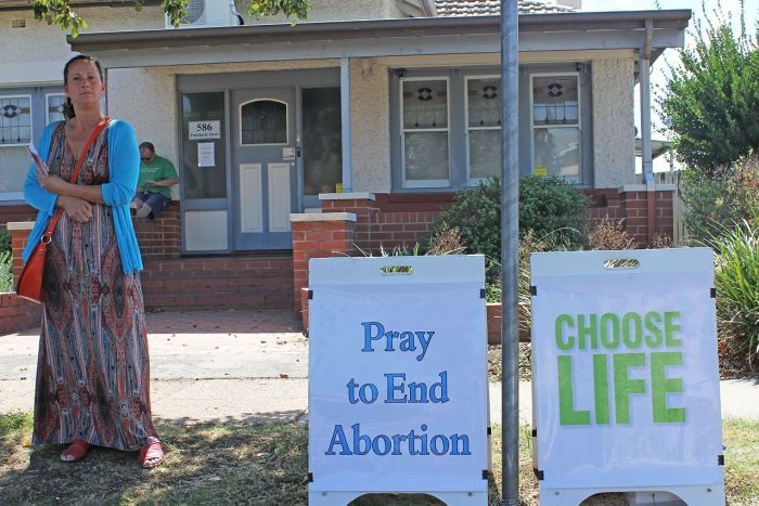 A woman stands outside of the Albury clinic protesting against abortion.