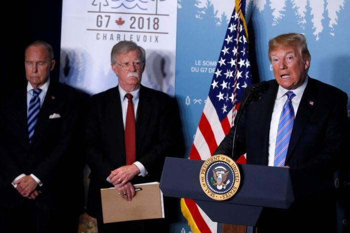 Donald Trump speaking at news conference at the G7 summit, standing next to John Bolton and Larry Kudlow.