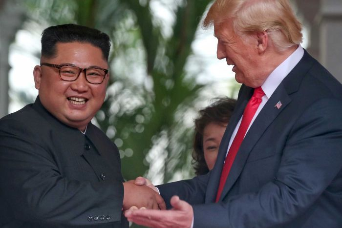 Donald Trump gestures as he talks to smiling Kim Jong-un.