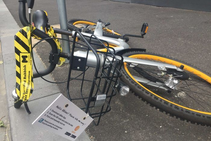An oBike lying on the street with yellow and black labelling it as dumped rubbish for investigation.