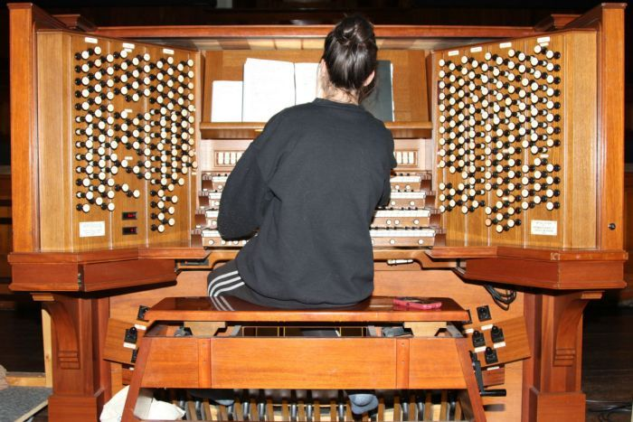 A woman sits at the portable organ console which controls the four-story high grand organ at Melbourne Town Hall.