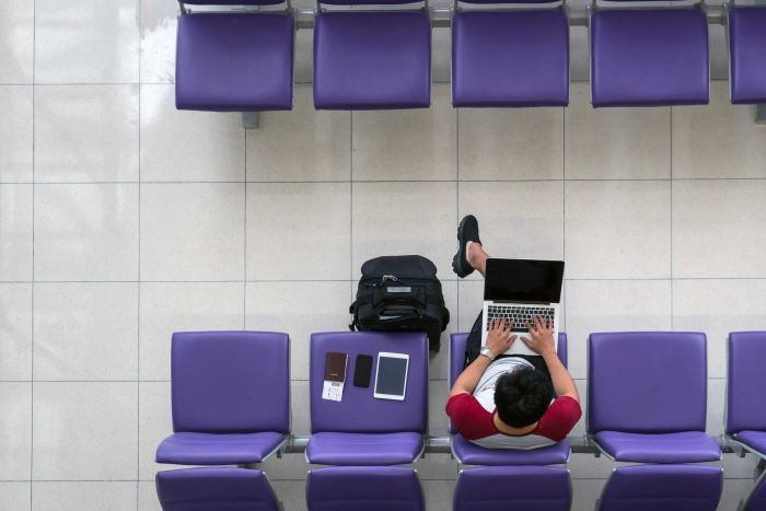 Aerial view of man working on laptop at an airport.