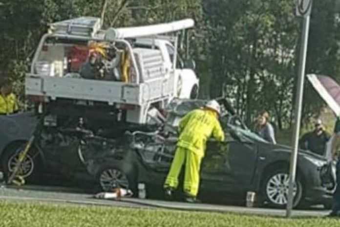 Emergency crews working on ute which landed on cars in Caboolture
