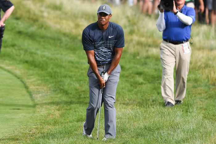 Tiger Woods looks into the distance standing in the rough with his golf club between his legs.