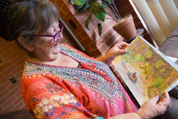 Di holds a painting she drew of a campsite