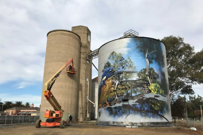 Two silos getting painted, the shorter of which is already decorated with an image of an azure kingfisher eating a golden perch