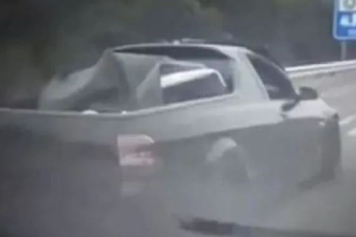 A black ute overtaking a car from the shoulder of the M1