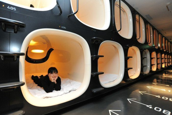 A woman lies in a capsule at a capsule hotel.