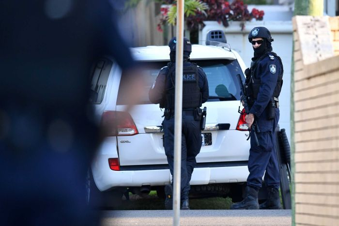 A police officer with a gun looks at the camera outside the Sunshine Coast siege