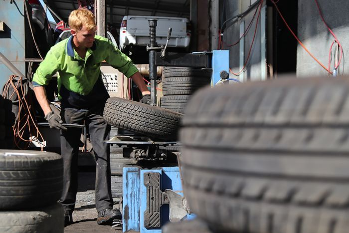 A fitter removes a tyre from a wheel rim at a recycling yard