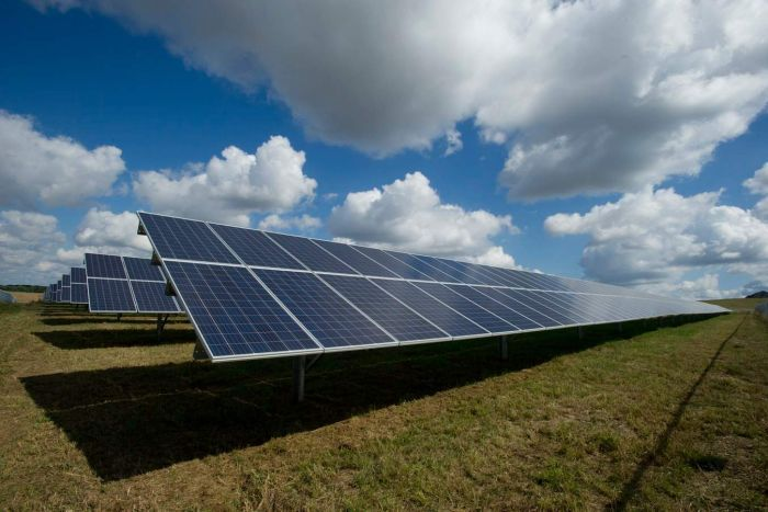 A row of solar panels in a field against a blue cloudy sky.