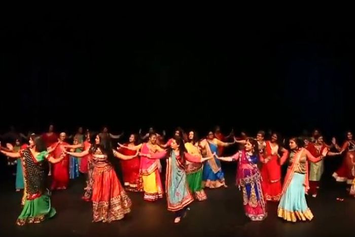 Women in bright colours and traditional Indian and Bhutanese dress dance on stage