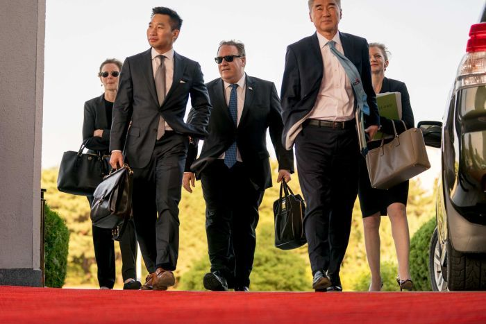 Secretary of State Mike Pompeo walks with other diplomats