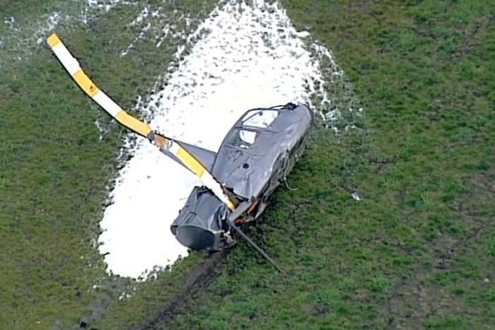 The crashed helicopter, missing its tail rotor, surrounded by fire retardant foam on the ground.