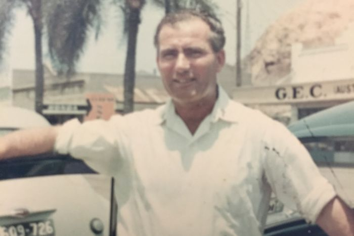 A man stands in front of a car in a photo taken in the 1960s.