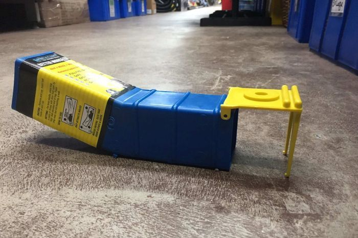A blue and yellow box that tilts up at one end and has a hole at the other end on the floor of a hardware store