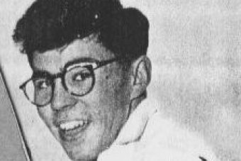 A black and white photo of a smiling man with thick black glasses.