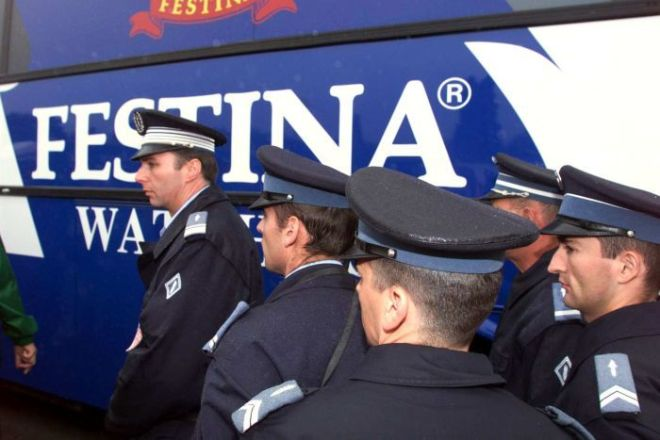 Policemen are on guard next to a Festina team bus before stage five of Tour de France, 1998.