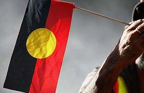 An elder holds an Aboriginal flag