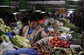 A woman shops for vegetables in a Beijing market.