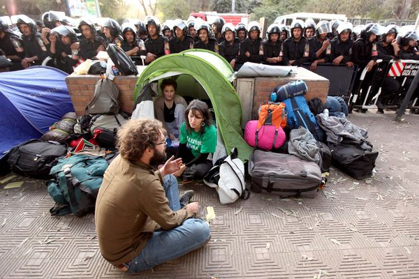 Foreign activists stage a sit-in in front of a row of riot police