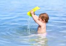 Bebé a brincar com a água na praia