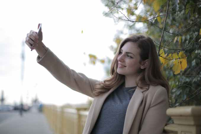 young woman in coat taking selfie with smartphone on street in overcast weather