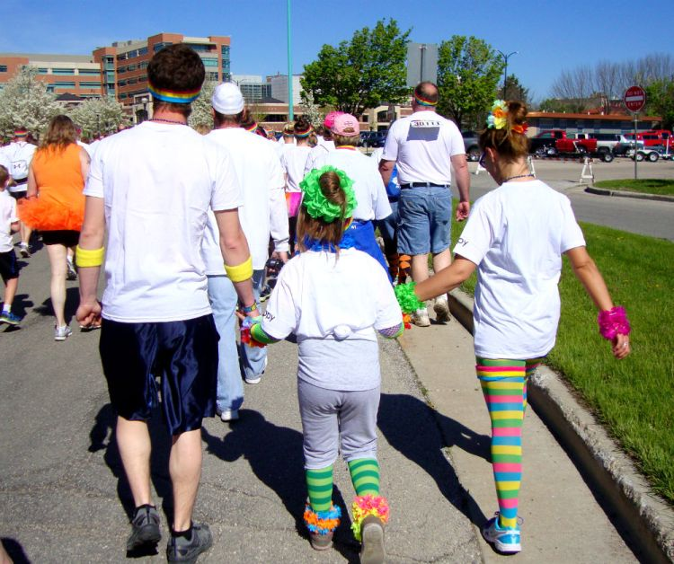 Family holding hands walking at a 5k Color Run.