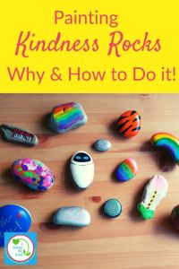 "A Table Filled with painted Kindness Rocks with text overlay ""Painting Kindness Rocks Why & How to Do it"""