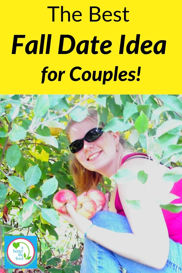 """Woman crouched under tree holding apples with text overlay """" The Best Fall Date Idea for Couples"""""""