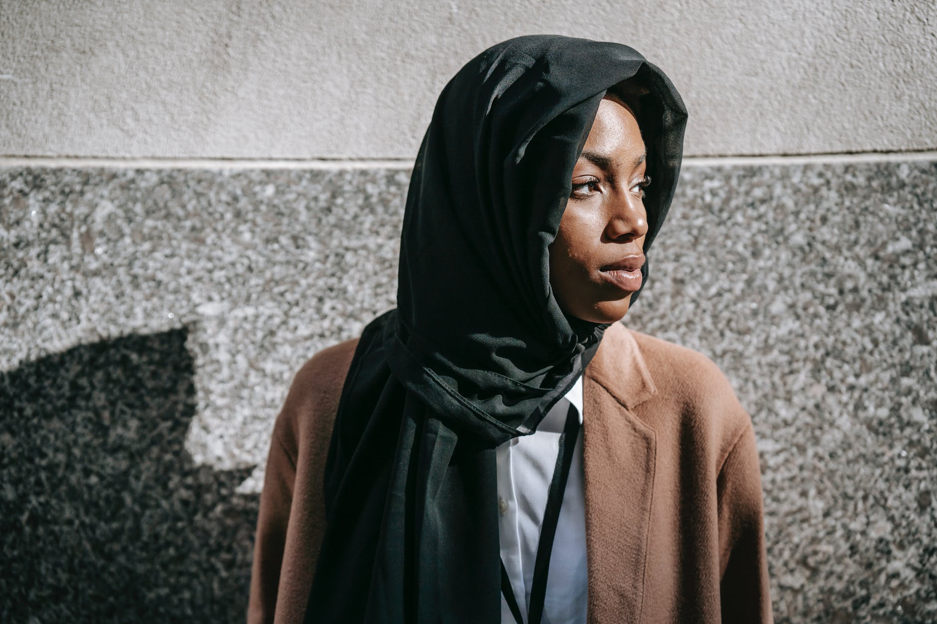 young muslim black woman in headscarf standing against marble wall