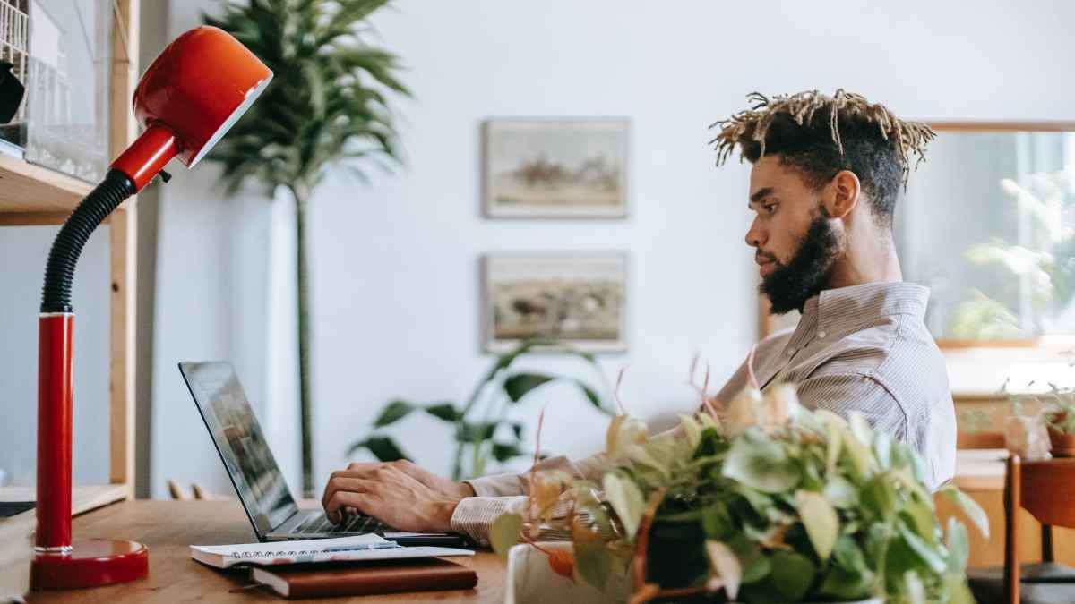 african american male freelancer on laptop in bright room