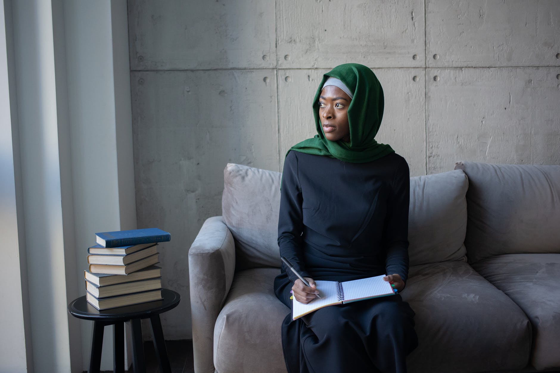islamic african american female in hijab on sofa with notebook