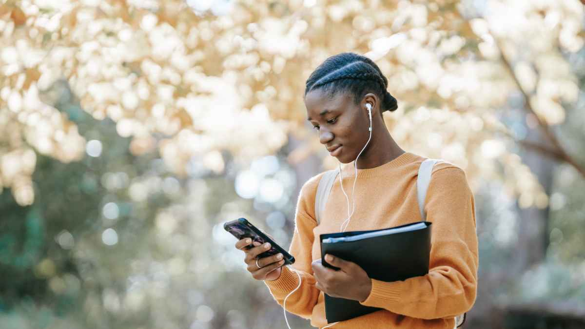 black student listening to music using smartphone in park