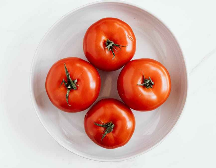 ripe tomatoes in ceramic bowl placed on marble table