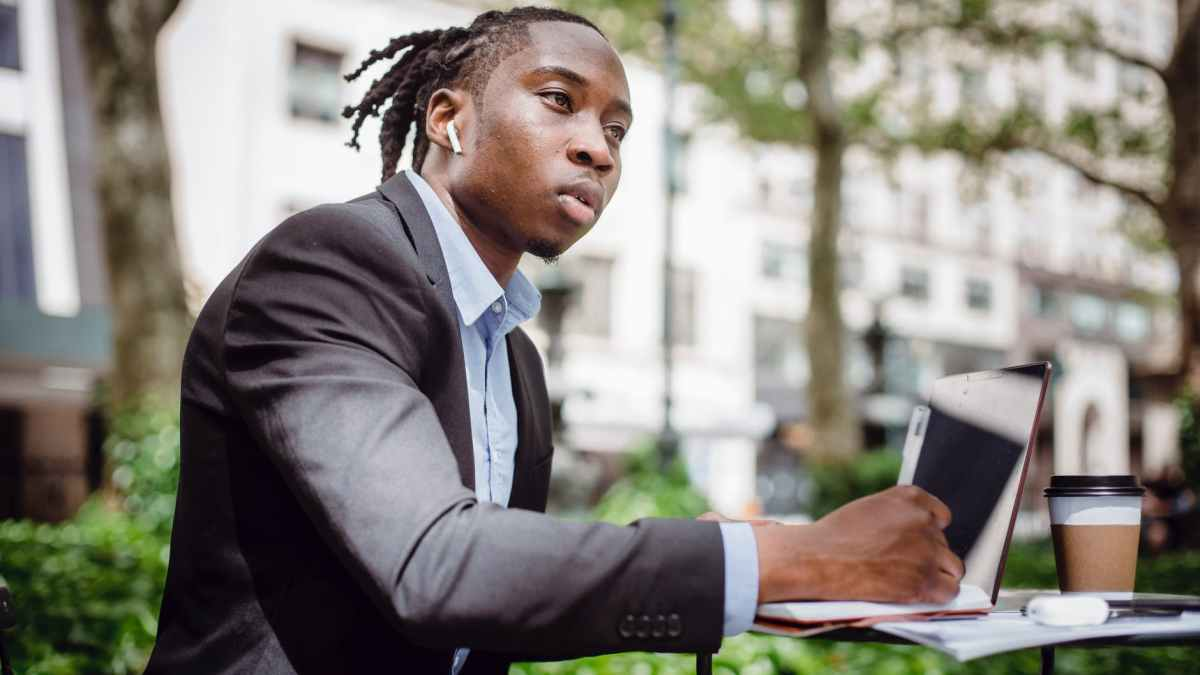 thoughtful black man writing in notebook sitting at table in outdoor cafeteria