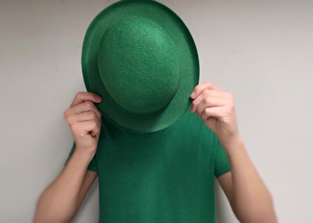 Man dressed for St. Patrick's day with hat over face.