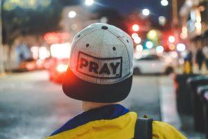 Man wearing PRAY cap