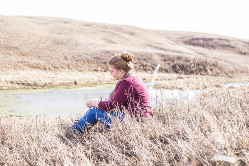 Woman sitting in grass thinking of trials