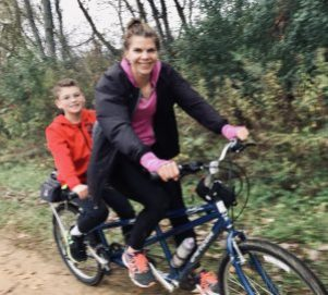Woman and son biking on tandem bicycle