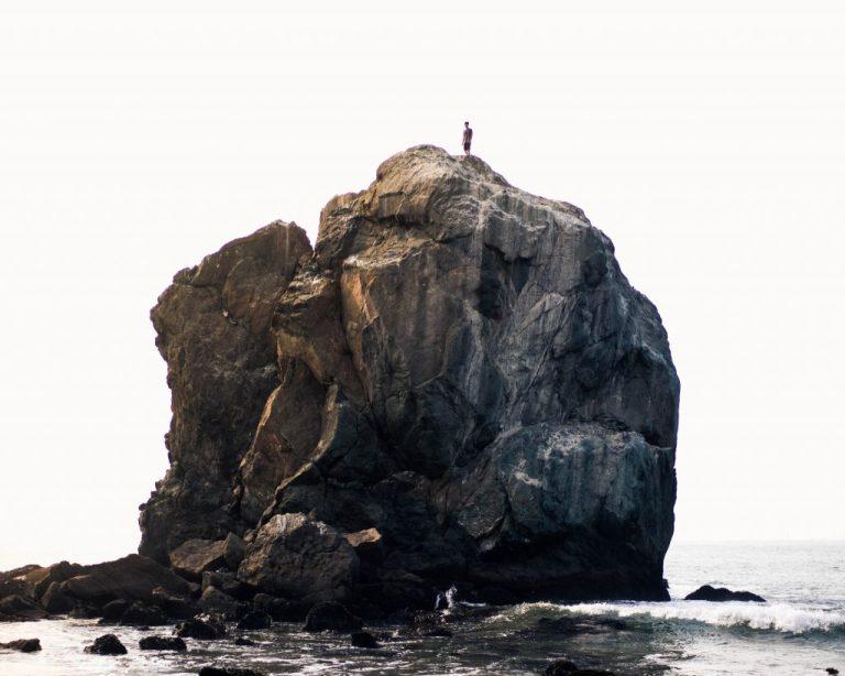 Man standing in strength atop massive rock in ocean.