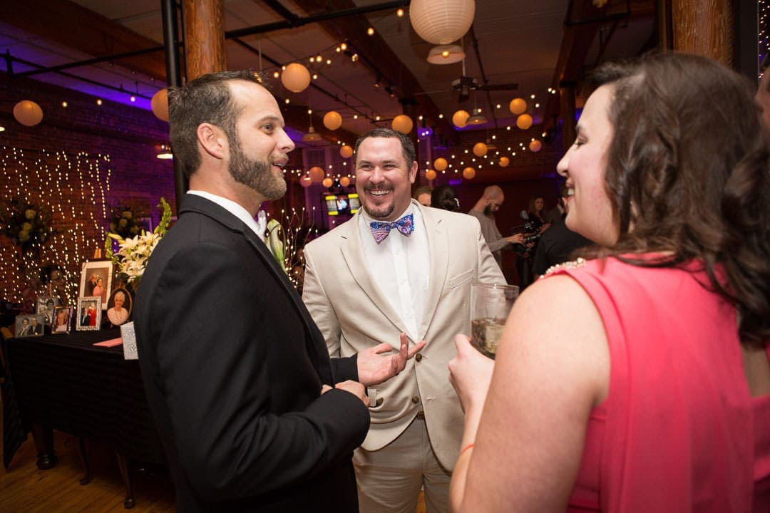 groom talking with friends at reception at city art gallery