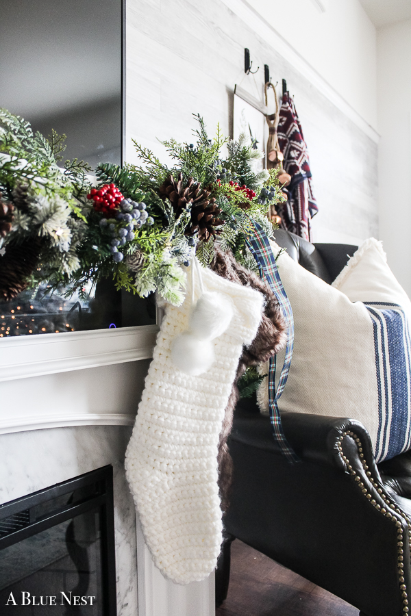 A simple Christmas home tour filled with greenery, touches of blue and red, cozy twinkle lights and a flocked tree with rustic touches.