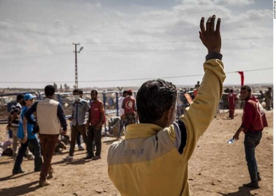 Faysal waves to relatives still waiting to enter Turkey from Syria.