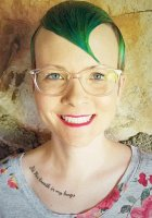 """Head shot photo of director Abra Singleton, with shock of vivid florescent green hair and tattoo under collar bone reading, """"It's His breath in my lungs"""""""