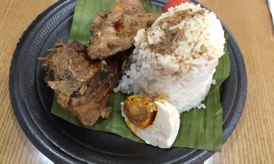 Chicken adobo with rice, and salted egg on banana leaf.