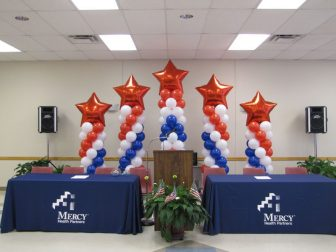 Set up a patriotic background for speakers with colorful columns