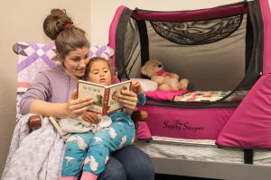 Mother reading to daughter in front of The Safety Sleeper