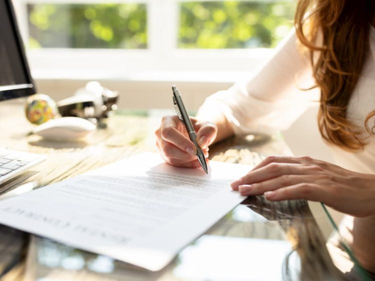 Person writing on a piece of paper at a desk