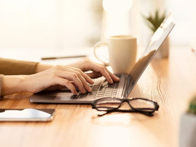 Person typing at a laptop with a mug and glasses on the desk beside them